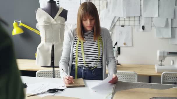 Junge Frau zieht sich im Editor während der Arbeit im Atelier Schneiderei Kleidung Skizze zu betrachten. Zeichnungen an der Wand hängen, sind helle Nähen Elemente sichtbar