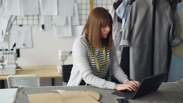 Mladé samice majitel malé krejčovství obchodu pracuje s notebookem její pracovišti. Nařídila textilie pro novou kolekci od místních textilní dodavatele.