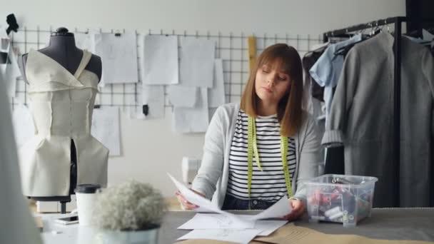 Krejčích obchod zaměstnanec je volba vlákna z krabice, srovnání barev, výběr perfektního tónu a jeho použití na oděvní design skici. Plánování budoucích oblečení kolekce koncept.