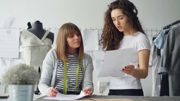 Professionelle Mode-Designerinnen sind Skizze betrachten und über Details des zukünftigen Kleidung zu diskutieren. Produktive Zusammenarbeit und schaffen neue sammlungskonzept