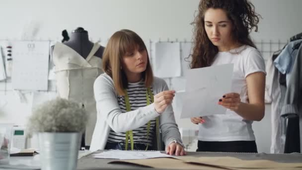 Young attractive women are looking at garment drawing and discussing it while working in modern sewing studio. Colleagues sharing ideas concept.