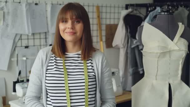 Portrét návrhář oblečení atraktivní mladá žena s hnědými vlasy při pohledu kamery. Usmívající se žena stojí vedle figuríny, lehké moderní krejčovské dílně v pozadí