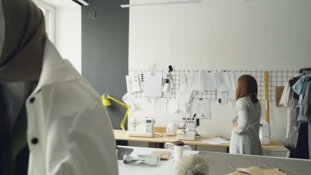 Attraktive Frau Kleidung Designer sucht nach Kleidungsstück Skizzen ...