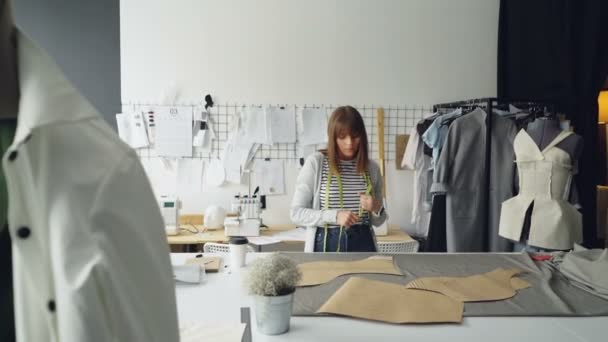 attractive seamstress is measuring clothing paper templates lying on