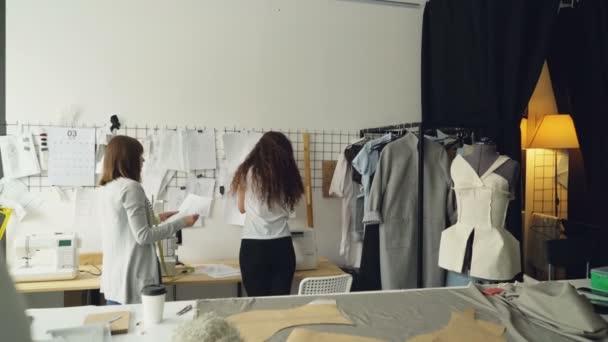 Jungunternehmer Kleidung Designer vor Wand mit hängenden Skizzen, Zeichnungen zu diskutieren und Platzieren von Bildern mit Clips. Kreativteam zusammen Arbeitskonzept