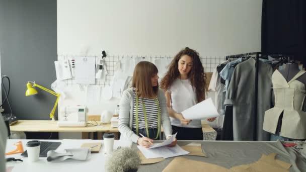 Mladá žena oblečení desigher je kreslení náčrtu, když její spolupracovník přichází k ní s návrhu, zobrazení a zlepšení image a diskutovat s kolegy