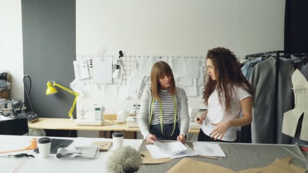 Young fashion designing entrepreneurs are discussing sketches of new clothes collection in their light studio. Women are looking through drawings, gesturing and talking.