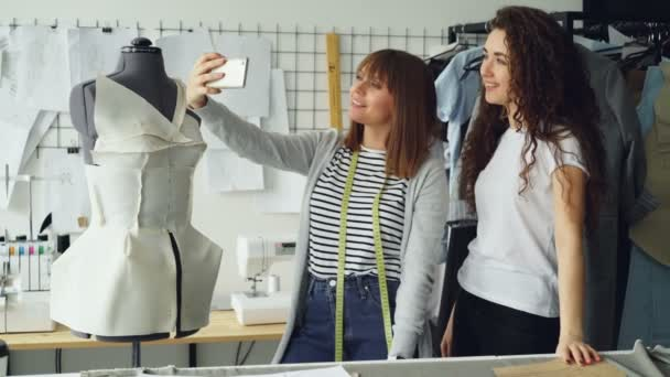 Two creative female designers are making selfie with smart phone while standing beside tailoring dummy in workplace. Attractive women are smiling and posing.