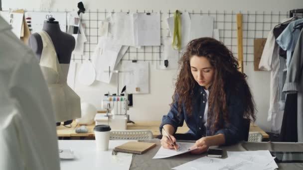 Mladá žena módní návrhář je kreslení náčrtu oděvu dámy na stůl v moderní dílně. Manekýn, šitím položky, káva na cestu jsou viditelné.
