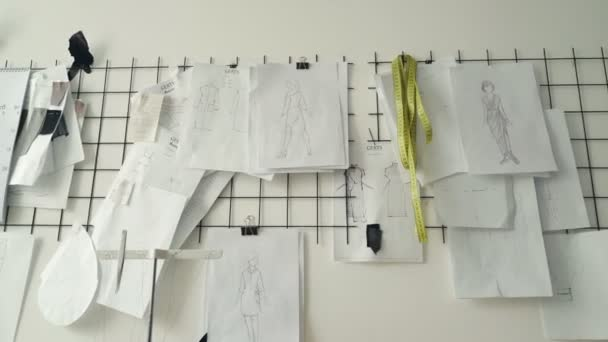 Clothing design sketches, black and white templates and drawings pinned on white wall in studio. Planning new clothes collection and creative thinking concept.