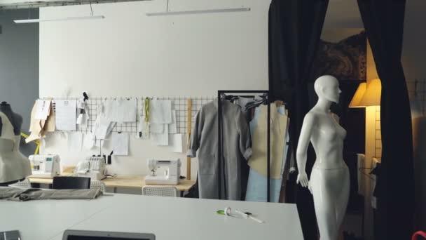 Pan záběr nalehko designérského studia s velkými krejčích stůl, panáky, četné skici připnul na zdi, šicí stroje a rozpracovaných oděvů na kolejích.