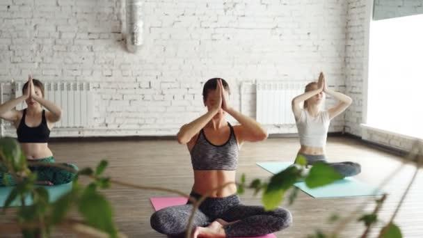 Mladé dívky duchovní dělají relaxační cvičení breating, jóga Studio. Jsou to namaste mudra, pak snížení ruce na kolena. Relaxační Seberozvoj energetické koncepce.