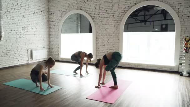 Dolly zastřelil cvičení jógy vede předklon pózy na světlé rohože leží na dřevěné podlaze v světelné studio mladých žen. Koncept zdravého životního stylu se těší
