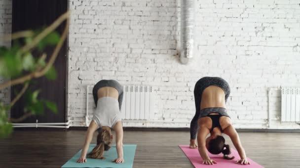 Mladá blondýnka se těší individuální jóga praxe s přátelskou ženské instruktor v světelné studio. Ženy dělají pořadí ásany na světlé rohože.
