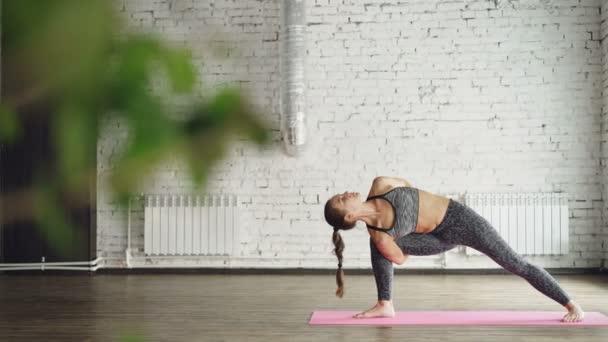 Pokročilý jóga student dělá kombinace vyrovnávání a moc ásany v moderní wellness centrum. Jóga pro zdraví, krásné tělo a relaxační koncepce