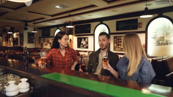 Two attractive young women and bearded young man are drinking beer sitting at bar counter, clinking and talking. Friends meeting in pub