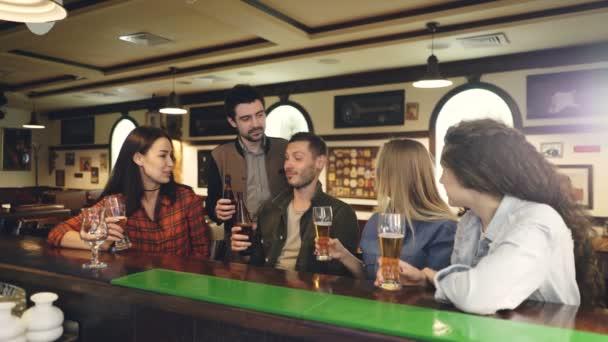 Gli studenti sono bere bar che celebra la fine della sessione accademica. Felici e socievoli giovani sono in chat, tostatura, fragorosi bicchieri e bottiglie e bere