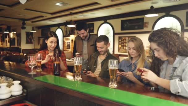 Young people are checking smartphones while sitting at bar counter together. They are showing each other screens, laughing and talking. Modern technologies communication concept.