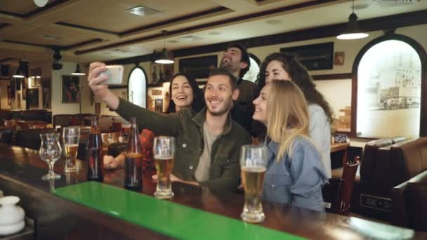 Young people are using smartphone to take selfie in popular bar. Friends are posing, having fun, gesturing and laughing.