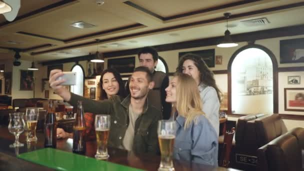 Group of friends are taking selfie via smartphone in nice pub. Beautiful people in casual clothes are posing and having fun. Friendly relaxing atmosphere, happiness concept.
