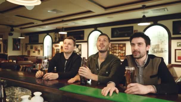 Tři fotbaloví fanoušci sledují zápas v sportsbar, fandění a oslavovat góly nad pivem. Muži jsou velmi emocionální, pokřikování a směřují