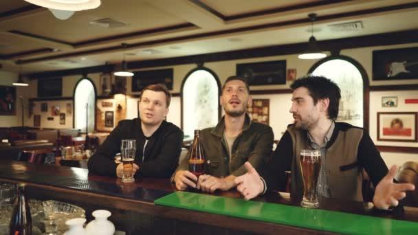 Allegri giovani uomini sono guardando la partita di calcio, tifo e bere birra seduti nel bar dello sport moderno. Gli accoppiamenti sono emotivo e felice