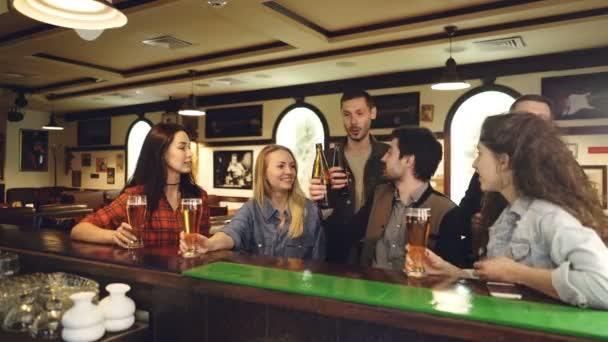 Skupina přátel v neformálním oblečení mluví, řinčení brýle a pití během setkání na čítač v seznamu vybrat ozdobný pruh. Komunikační zábavní slavnost koncept.