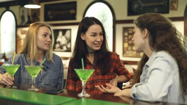 Cheerful female students are talking emotionally when sitting at counter in pub. Girls in casual clothes are sharing news and laughing. Youth having fun in free time concept.