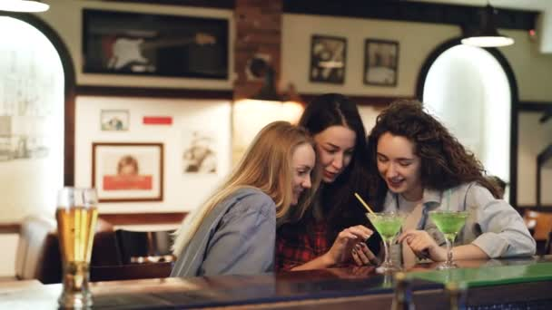 Girls are using smartphone, laughing and talking while sitting in bar together. Girls in casual clothing are watching screen and chatting. Modern technologies for fun concept.