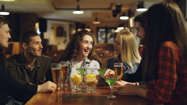 Good-looking young people are having fun, drinking and socializing in fancy bar together. Friends are happy, they are enjoying night out in good company.