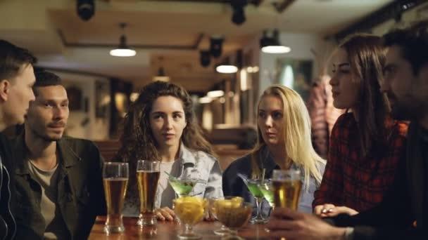 Dobře vypadající mladí přátelé sdílejí novinky, posezení v kavárně u stolu s občerstvením a nápoji. Kamarádi si užívají večer. Přátelské neformální atmosféra