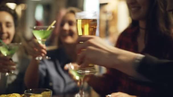 Šest rukou cinkání sklenic piva a koktejlů v útulné kavárně. Šťastné tváře krásných mladých lidí pití alkoholu v pozadí. Mládež slaví svátek koncept