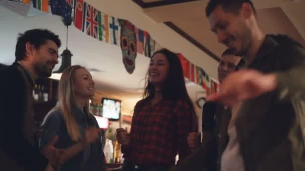 Šťastné mladé lidi v neformálním oblečení se tančí v moderním baru. Se smíchem a chatování, Bavíte se spolu. Milénia těší noční život koncept