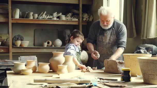Veselý chlapeček je házel kousky jílu na pracovním stole zároveň pomáhá jeho dědeček v dílně hrnčíře. Šťastné dětství, rodinné tradice a hobby koncepce.