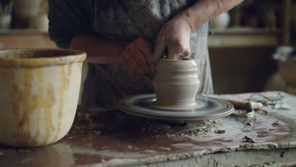 Tilt-up shot Professional potter a vytváření jar od hnědé hlíny pracovišti pomocí házení kola. Tradiční keramika, ručně vyráběné nádobí a pracovití lidé koncepce.