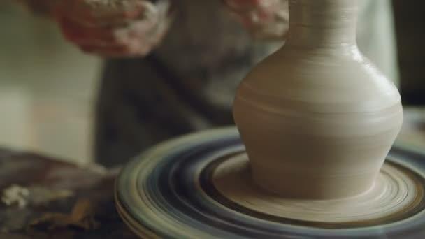 Práce v keramické dílně: hliněné nádobí na házení kola, hlavní keramik formovat jílu pomocí nástrojů. Keramické nádobí a tradiční okupace koncept.