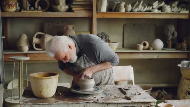 Skilled elderly potter is producing ceramic pot on turning wheel in workplace. Creation process, traditional pottery and interesting hobby concept.