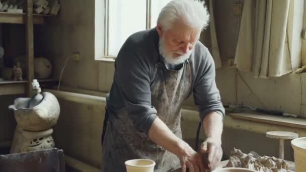 Erfahrene männliche Potter ist mischen und kneten von Lehm am Arbeitstisch während der Arbeit in kleinen Werkstatt mit professioneller Ausrüstung, Werkzeuge und viele keramische Figuren