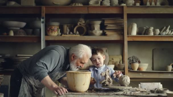 Cute small boy is playing with clay making ceramic toy in his grandfathers workshop. Grey-haired bearded man is looking at him with love and pride and talking.