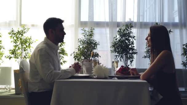 Boční pohled na mladý pár sedí společně u stolu v restauraci a mluví držel ruku. Romantické vztahy, luxusní restaurace a mladých lidí koncepce