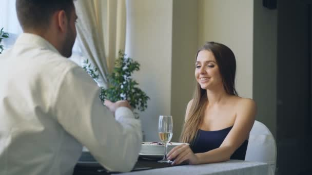 Pretty girl in beautiful dress is saying yes to marriage proposal, taking engagement ring, drinking champage and looking at jewelry with delight. Love and romance concept.