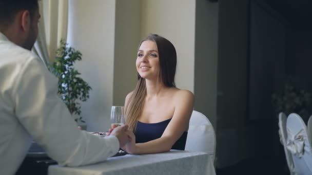 Attractive young woman is saying yes to marriage proposal and her boyfriend is putting engagement ring on her finger. Romantic relationship and restaurant date concept.