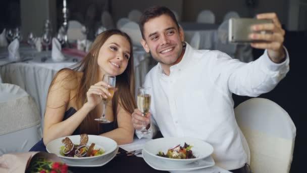 Das attraktive Liebespaar macht beim Abendessen im Restaurant ein Selfie mit Champagnergläsern per Smartphone. Sie lächeln, küssen und posieren in die Kamera.
