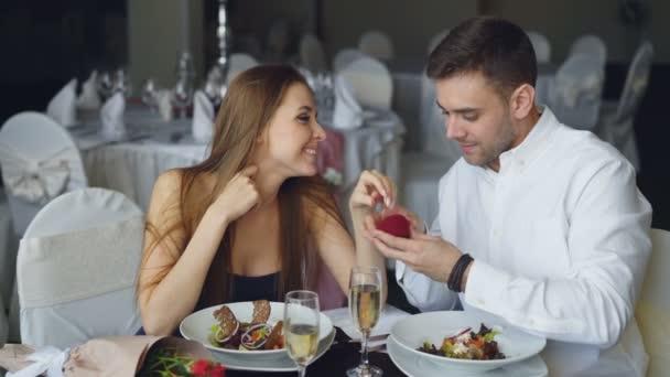 Donna attraente è dire sì alla proposta di matrimonio e il suo ragazzo è mettere lanello di fidanzamento al dito e baciarla. Concetto di data di relazione e ristorante romantico