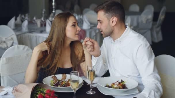 Šťastné milující pár se drží za ruce, mluví a líbání při romantické večeři v restauraci. Láskyplný vztah, láska a jemné jídelní koncepce.