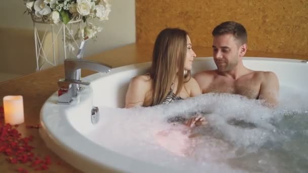 Young attractive people are hugging and talking in bubbling bathtub with foam in modern day spa. Romantic relationship, conversation and wellness concept.