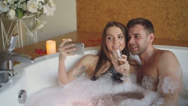 Das entzückende junge Paar macht mit dem Smartphone ein Selfie mit Champagnergläsern, während es in der Badewanne badet. Sie lächeln, küssen und posieren in die Kamera.
