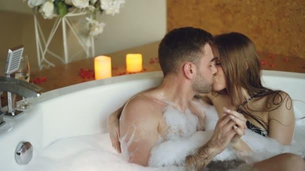 Giovani amanti attraenti in costume da bagno sono abbracci e baci in jacuzzi con schiuma nella - Fare sesso in bagno ...