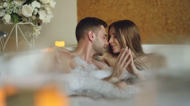 Das frisch verheiratete Paar entspannt sich im Whirlpool, küsst sich, berührt die Hände, redet und lacht. romantische Beziehung, leidenschaftliche Flitterwochen und Wellness-Konzept.