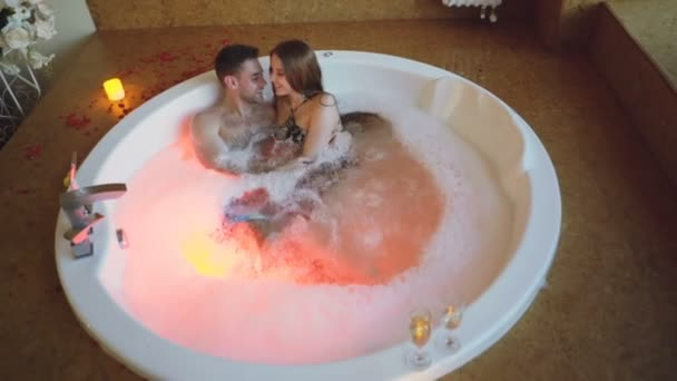 Blick aus der Vogelperspektive auf junge Leute in Badeanzügen, die sich im Whirlpool mit Schaumstoff im Day Spa unterhalten, umarmen und küssen. romantische Beziehung, Leidenschaft und Wellness-Konzept.